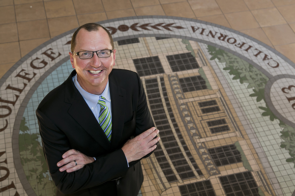 Greg Schulz, Ed.D., president of Fullerton College, stands in front of a mosaic seal for the college.