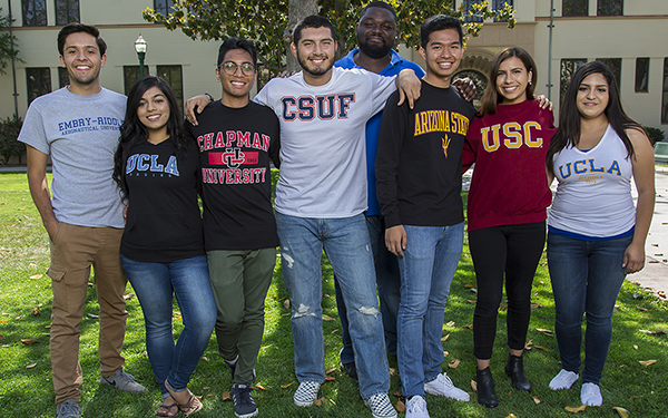 A group of Fullerton College students stands wearing T-shirts representing the colleges to which they will soon be transferring.