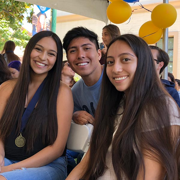 3 students smiling at camera. Photo.